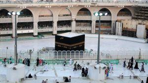 Några människor promenerar runt Kaaba i den stora moskén i Mecka 5.3.2020. Saudiarabien desinficerar muslimska heliga platser, och har inhiberat den årliga heliga pilgrimssammankomsten umrah.