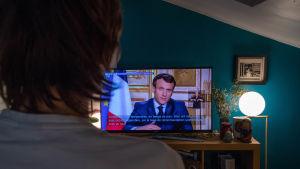 Fransk person tittar på Emmanuel Macrons tv-tal om coronaläget.