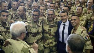 Frankrikes president omfamnar soldater stationerade i Mali under ett besök.