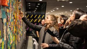 Olika personer tittar på och tar bilder med mobilen av ett pussel upphängt på väggen.