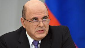 Misjustin sitter med Rysslands färger i bakgrunden.