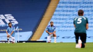 Burnleys och Citys spelare knäböjer inför matchen.