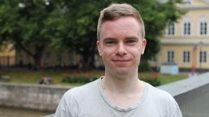 En blond ung man ser in i kameran och ler.