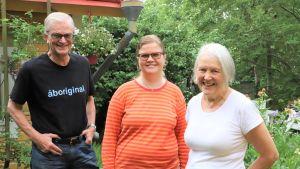 Tre personer, en man och två kvinnor, står på en grönskande gård i Raunistula.