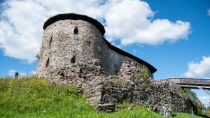 En sommarbild på raseborgs slott i en grön miljö.