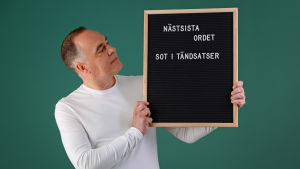 """Jens Berg håller i en svart skylt med texten: """"Näst sista ordet, sot i tändsatser""""."""