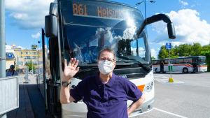 En man framför en buss.