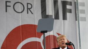 Donald Trump står och talar i en mikrofon på en scen.