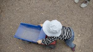 Litet barn i randiga kläder och ljusblå mössa leker med en stor leksaksbil på ett underlag av sand.