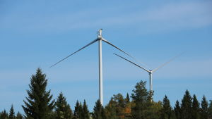 Två vindkraftverk står i skogen. På det främre kraftverket saknas ett rotorblad.