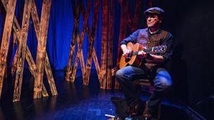 Håkan Omars ramar in berättelsen med sin gitarr.