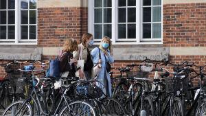 Ungdomar går på en gata med många parkerade cyklar. De bär munskydd.