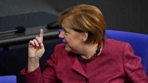 Angela Merkel tittar åt sidan och håller upp ett finger