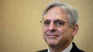 En man med grått hår och glasögon ler och tittar in i kameran.