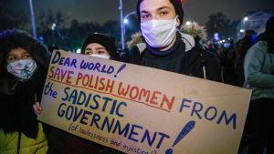 En person håller upp plakat under demonstration i Polen.
