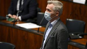 Anders Adlercreutz i munskydd står och talar i riksdagen.