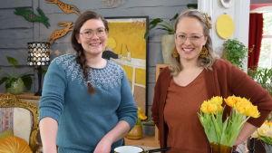 En kvinna med brunt, långt hår i fläta, glasögon och en blå stickad tröja tillsammans med en annan kvinna som är programledare för tv-programmet Strömsö.