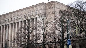 Massivt stenhus med en pelarrad på framsidan. Riksdagshuset i Helsingfors.