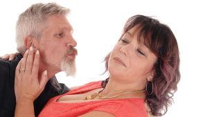 äldre man som försöker kyssa en äldre kvinna men hon vill inte