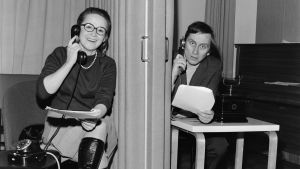 Marjatta Kallio ja Esa Saario puhelimien kanssa verhon erottamina kuunnelmassa Koulussa ei sovi kummitella.