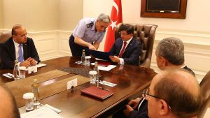 Chefen för det turkiska flygvapnet Akin Ozturk talar med Turkiets premiärminister Ahmet Davutoglu.