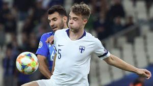 Leo Väisänen i närkamp med en grekisk spelare i ryggen.