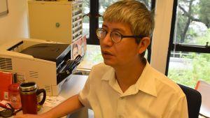 Professor Ma Ngok sitter vid sitt skrivbord.