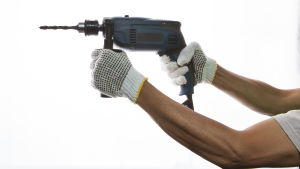 Två händer håller i en borrmaskin.