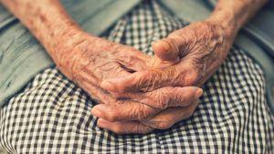 Ett par knäppta händer som tillhör en gammal person.