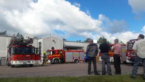 Arbetstagare vid Stera Technologies väntar utanför industribyggnaden i Pemar där det brunnit, medan brandmän utför eftersläckning.