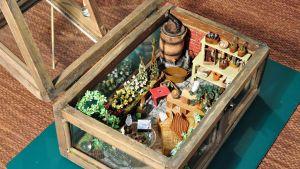 ett av tittskåpen föreställer ett växthus som innehåller blommor och träd, krukor och gamla tidningar, en fotölj och ett glasbord och många andra små detaljer.