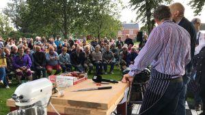 Michael Björklund och Matias Jungar kockar inför en stor publik som sitter i en park.