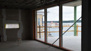 Foto taget i en bostad som hålls på att byggas. Genom glasdörrarna ser man stadsfjärden i Ekenäs och restaurang Knipan.