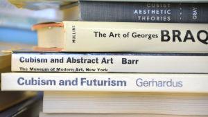 Bokryggar av konstböcker i närbild.