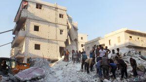 Invånare och medlemmar av frivilligkåren Vita hjälmarna letar efter överlevande i en husruin efter flygräder mot staden Harim i Idlib-provinsen.