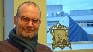 Porträtt på museichef Kai Kartio med foto på Amos Andersson i bakgrunden.