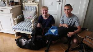 En kvinna och en ung man sitter på golvet och leker med två stora svarta diabeteshundar.