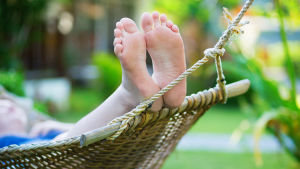 Fötterna på en person som ligger i en hängmatta.