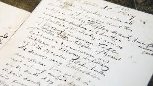 En gammal handskriven obduktionsrapport. Det går inte att läsa vad som står eftersom handstilen är dålig samt väldigt gammaldags.
