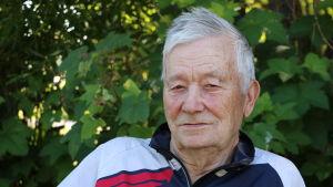 En man i 80-årsåldern sitter framför en buske.