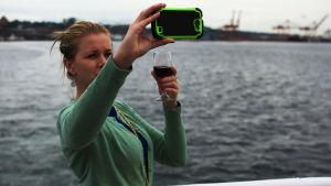 En kvinna dricker vin och tar en selfie.