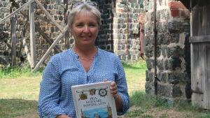 Carina Wolff-Brandt står bland gamla slaggstensbyggnader med sin nya bok i händerna och ser glad ut.