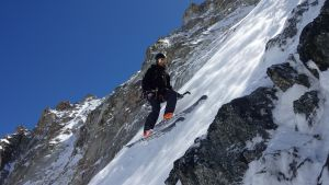 En person står på en mycket brant bergsvägg. Hen har på sig slalomhjälm och skidor.