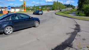 två bilar i en rondell där vägbeläggningen har skalats bort