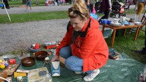 Karin Hakula sitter på huk och håller i ett gammalt Sirkku-paket med socker.