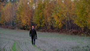 Magnus går på åkern, orange höstlöv i bakgrunden.