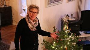 En kvinna med glasögon står bredvid en julgran.