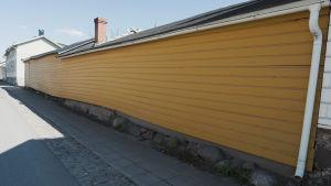 Puutalon keltaiseksi maalattu seinä