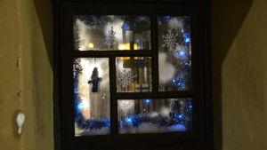 Ett källarfönster med glitter, tomtar och Finlands flagga.