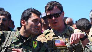En amerikansk officer samtalar med en YPG-soldat